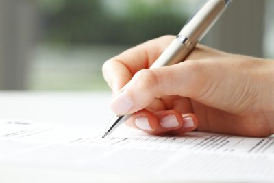 woman using silver pen to sign paperwork